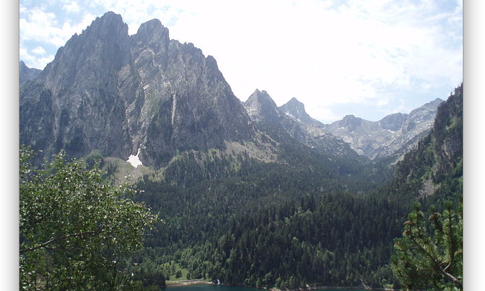 The Enchanted, two emblematic peaks of the Pyrenees and the San Mauricio pond. Encantats in Aigüestortes National Park. Lleida, Spain. (Wikimedia Commons)