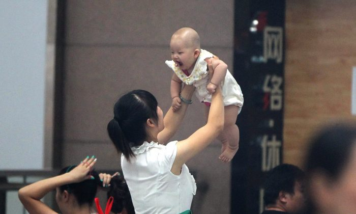 A woman holds her baby in Zhengzhou, in central China's Henan Province on July 29, 2014. Recent reports in China's state-run media have told of the excessive profits, exploitation of surrogate mothers, and sex-selective abortions that accompany the business of surrogacy. (STR/AFP/Getty Images)