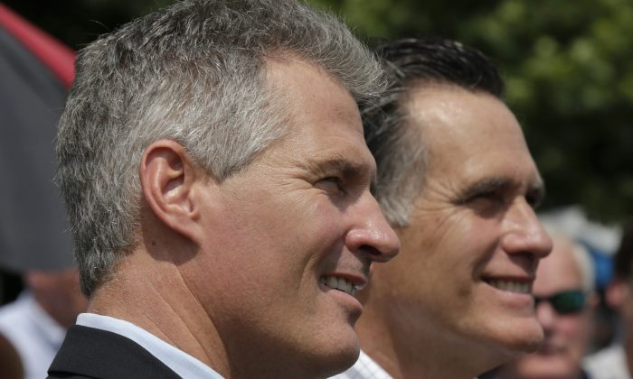 New Hampshire Senate candidate Scott Brown, left, stands with Mitt Romney, the former Republican presidential nominee, as they wait to be introduced during a campaign stop at a farm in Stratham, N.H., Wednesday, July 2, 2014.  Brown, who is facing incumbent Democrat U.S. Sen. Jeanne Shaheen, was endorsed by Romney at the event.  (AP Photo/Charles Krupa)