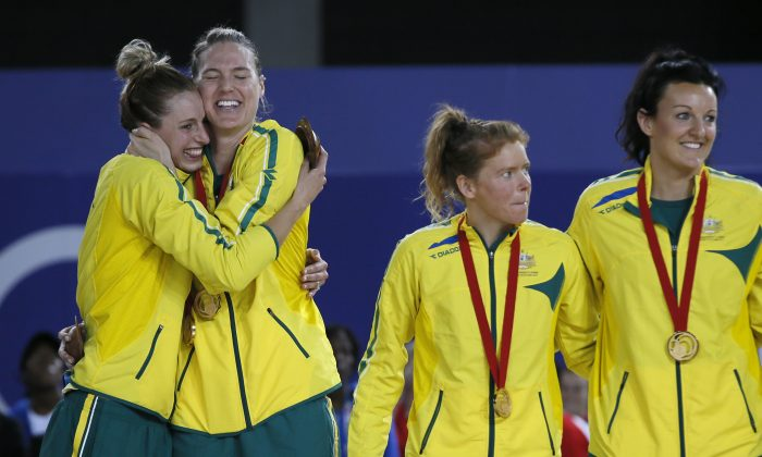 Laura Geitz, left and Caitlin Bassett, of Australia hug after they received their gold medals as they stand on the podium during the medal ceremony, after they defeated New Zealand in the gold medal match in the women's Netball at the Commonwealth Games Glasgow 2014, in Glasgow, Scotland, Sunday, Aug., 3, 2014. (AP Photo/Alastair Grant)