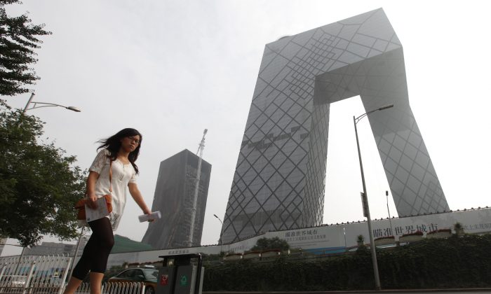 A woman walks pass the China Central Television (CCTV) complex in Beijing on Aug. 13, 2010. Investigations into CCTV staff have recently accelerated. (Franko Lee/AFP/Getty Images)