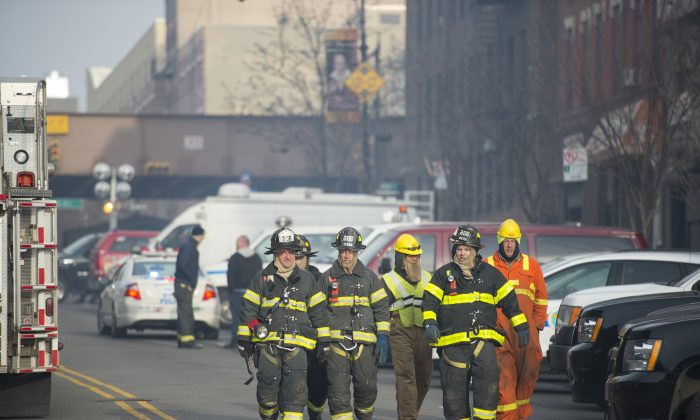 Firefighters working in Harlem, N.Y., on March 13, 2014. Governor Andrew M. Cuomo signed legislation on Monday, calling for stricter background checks on potential volunteer firefighters as a measure to protect children and families. (Dai Bing/Epoch Times)