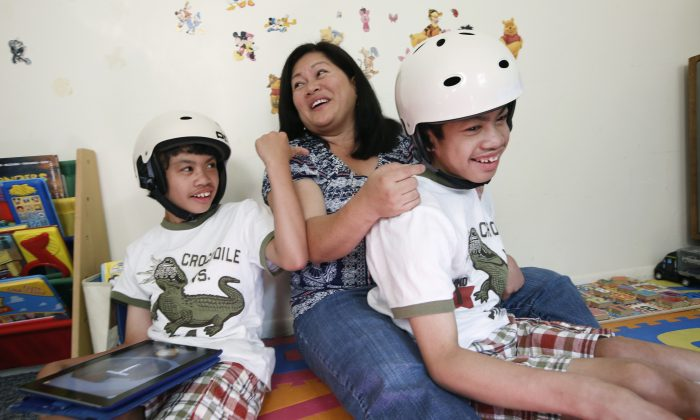 Arlene Aguirre (C) plays with her formerly conjoined twin sons, Clarence (L) and Carl, 12, at the family's home in Scarsdale, N.Y., Thursday, July 31, 2014. On Monday, Aug. 4, the family will celebrate the 10th anniversary of the risky surgery in which the boys were separated at Montefiore Hospital, where the surgery was initially performed. (AP Photo/Kathy Willens)