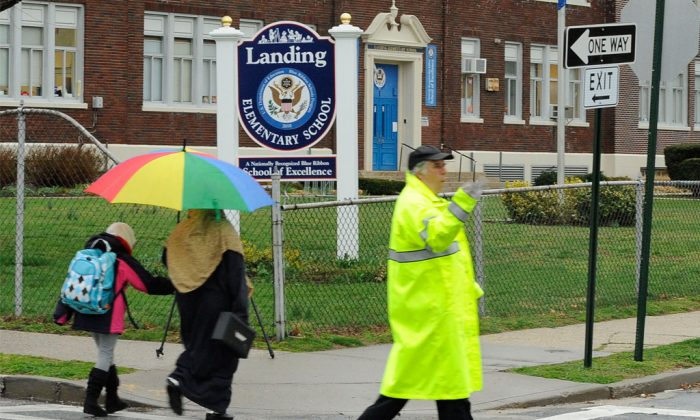 A student and her mother pass a crossing guard as they arrive at Landing Elementary School in Glen Cove, N.Y., Friday, April 12, 2013. A new law is raising the penalty for assaulting crossing guards doing their jobs. (AP Photo/Kathleen Malone-Van Dyke)