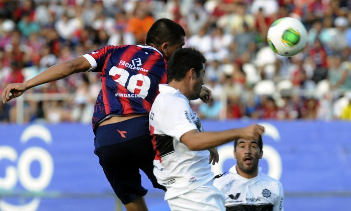 Olimpia's Juan Dante Lopez (R) vies for the ball with Junior Alonzo, of Cerro Porteno, during Paraguay's Clausura tournament football derby , on November 10, 2013, at the Defensores del Chaco stadium, in Asuncion. (NORBERTO DUARTE/AFP/Getty Images)