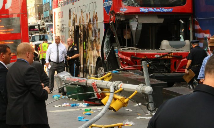 First responders in front of tour coaches damaged in a collision in Times Square, New York City, on August 5, 2014. (Brendon Fallon/Epoch Times)
