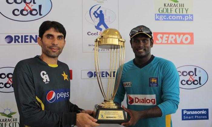 Sri Lankan cricket captain Angelo Mathews, right, and his Pakistani counterpart Misbah-ul-Haq pose for photographers with the series trophy ahead of their first test cricket match against Pakistan in Galle, Sri Lanka, Tuesday, Aug. 5, 2014. (AP Photo/Eranga Jayawardena)