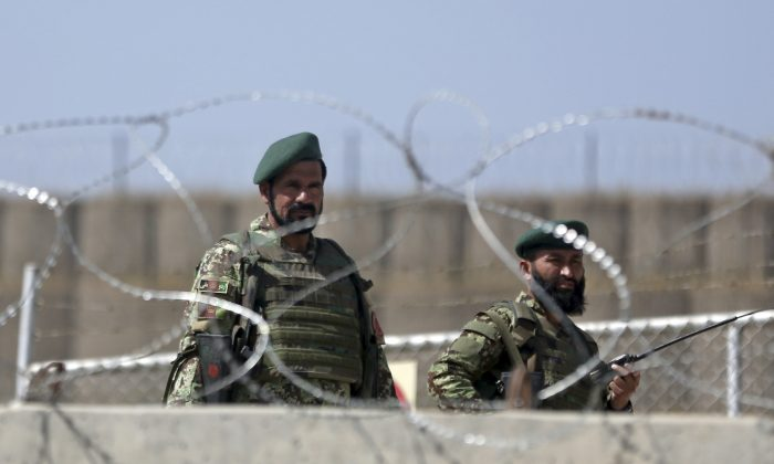 Afghanistan National Army soldiers stand guard at a gate of Camp Qargha, west of  Kabul, Afghanistan, Tuesday, Aug. 5, 2014. (AP Photo/Massoud Hossaini)