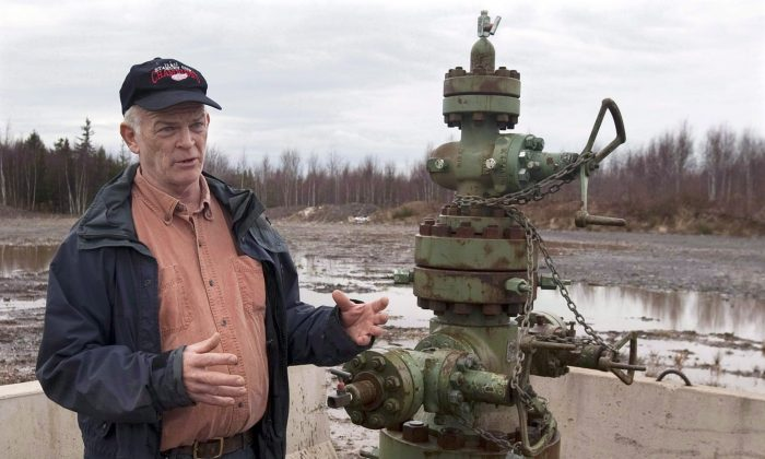 Nova Scotia resident Ken Summers stands next to a wellhead for an exploratory natural gas well near his home on Dec. 6, 2013. A new Wikipedia-style website aims to provide information on the 4 million oil and gas wells throughout Canada and the U.S. that have been drilled since 1859. (The Canadian Press/Andrew Vaughan)