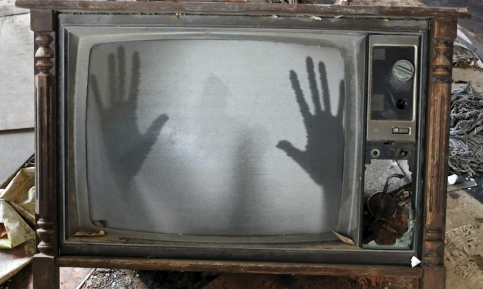 A concept image of a ghost appearing on a flickering television set. Could the dead communicate through electronics as some have claimed? Dr. Imants Barušs investigates. (Thinkstock)