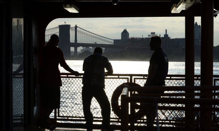 With the Brooklyn Bridge in the background, commuters on the Staten Island Ferry watch the morning sunrise in the New York Harbor in lower Manhattan, on July 11, 2014. (Timothy A. Clary/AFP/Getty Images)