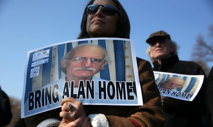 In this file photo, supporters hold signs to call on bringing home of U.S. citizen Alan Gross who was being held in a Cuban prison, during a rally at the Lafayette Park outside the White House December 3, 2013 in Washington, DC. (Photo by Alex Wong/Getty Images)