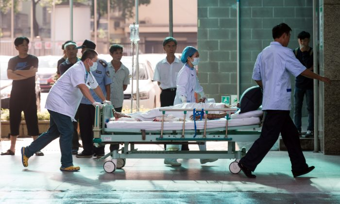 Doctors and nurses rush a victim of a factory explosion for treatment at a hospital in Kunshan in eastern China on Aug. 2, 2014. (Johannes Eisele/AFP/Getty Images)