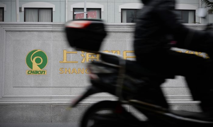 A motorbike rider rides past the gate of the faculties of Chaori Solar Energy Science & Technology Co. in Shanghai on March 8, 2014. Chaori was China's first-ever default on a domestic corporate bond. (STR/AFP/Getty Images)