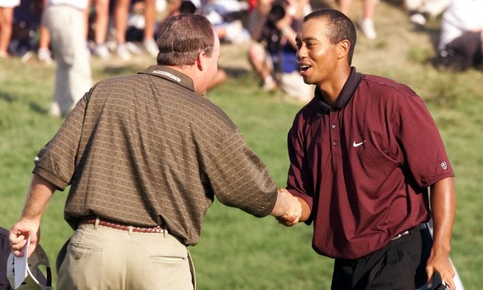 Golfer Tiger Woods (R) of the US shakes hands with fellow countryman Bob May (L) after their final putts on the 18th hole 20 August 2000 to force a playoff in the 82nd PGA Championship at Valhalla Golf Club in Louisville, KY. Woods and May where forced to play a three hole playoff when they tied after 72 holes. (JEFF HAYNES/AFP/Getty Images)