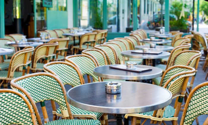 Street view of a coffee terrace with tables and chairs,paris France. (*Shutterstock)