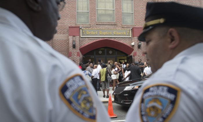 In this July 23, 2014, photo, a pair of New York City police officers stand at their post as mourners arrive for the funeral service of Eric Garner at Bethel Baptist Church in the Brooklyn borough of New York. Garner died on July 17, 2014. (AP Photo/John Minchillo)