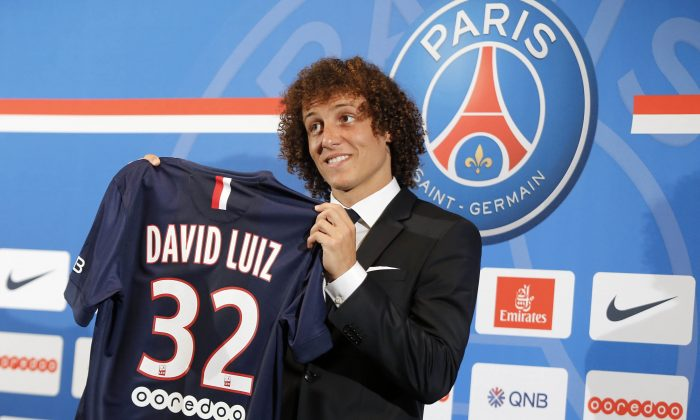 Brazil's David Luiz  holds his soccer shirt, as he poses for photographers following a press conference, in Paris, Thursday, Aug. 7, 2014. Defender Luiz believes the only way to get over his World Cup disappointment is to be back on the pitch as quickly as possible. French champion Paris Saint-Germain signed Luiz on a five-year deal that was announced before his lackluster performances in Brazil's last two games at the World Cup last month. (AP Photo/Jacques Brinon)