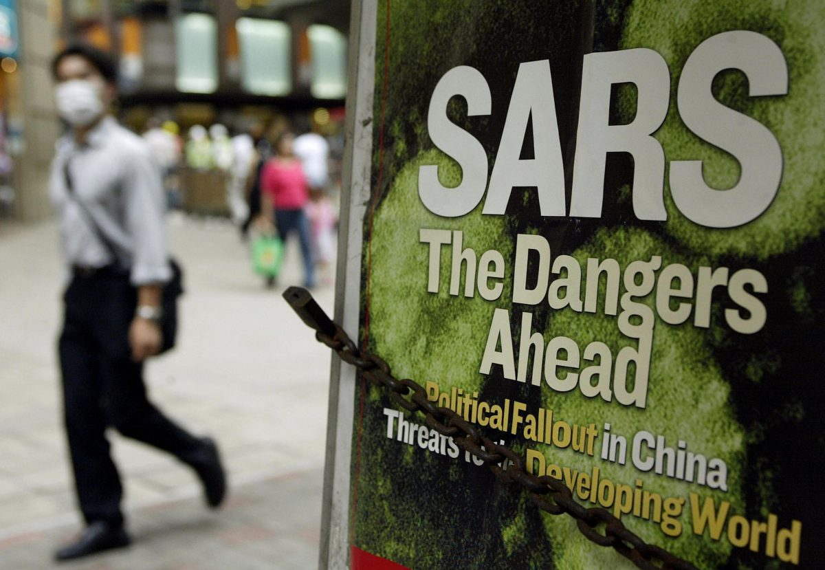 A man wearing a mask to protect himself from SARS, walks by a news headline at a newsstand on a street in Hong Kong, in May 2003. (Peter Parks/AFP/Getty Images)