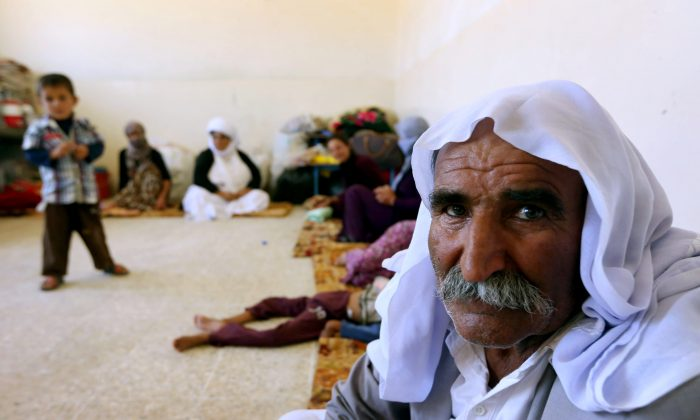 An Iraqi Yazidi family that fled the violence in the northern Iraqi town of Sinjar, sit at at a school where they are taking shelter in the Kurdish city of Dohuk in Iraq's autonomous Kurdistan region, on Aug. 5, 2014. Islamic State (IS) Sunni jihadists ousted the Peshmerga troops of Iraq's Kurdish government from the northern Iraqi town of Sinjar, forcing thousands of people from their homes. The Yazidis, are a small community that follows a 4,000-year-old faith and have been repeatedly targeted by jihadists who call them 'devil-worshipers' because of their unique beliefs and practices. (Safin Hamed/AFP/Getty Images)
