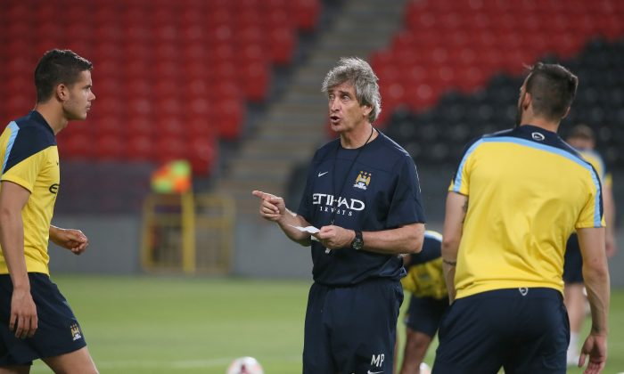 Manchester City manager Manuel Pellegrini speaks with his players during a training session at the Sheikh Mohammed Bin Zayed Stadium in Abu Dhabi, on May 14, 2014, prior to their friendly match against UAE's Al-Ain Club. (KARIM SAHIB/AFP/Getty Images)