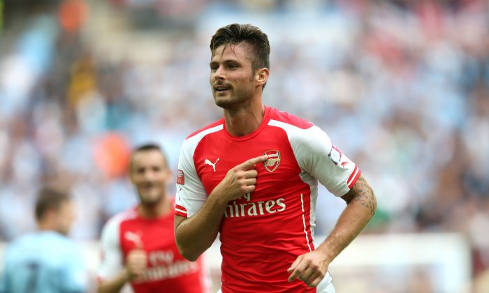 Olivier Giroud of Arsenal gestures to the badge on his shirt after scoring the third goal during the FA Community Shield match between Manchester City and Arsenal at Wembley Stadium on August 10, 2014 in London, England. (Photo by David Rogers/Getty Images)