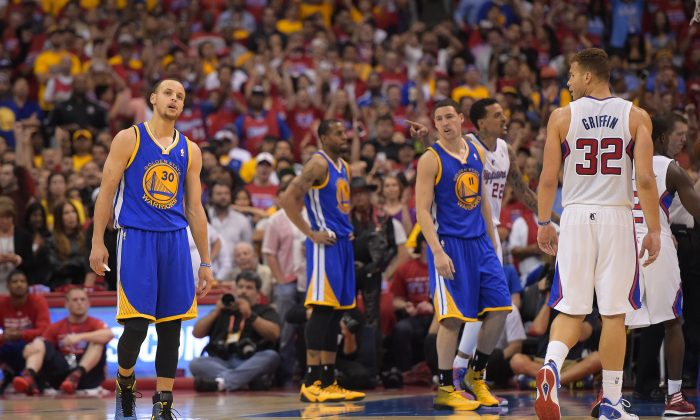 Los Angeles Clippers forward Blake Griffin, right, looks over at Golden State Warriors guard Stephen Curry, left, in the closing seconds in Game 7 of an opening-round NBA basketball playoff series, Saturday, May 3, 2014, in Los Angeles. The Clippers won 126-121. (AP Photo/Mark J. Terrill)