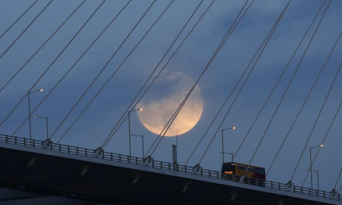 """A perigee moon, also known as a super moon, raises over a bridge in Hong Kong Sunday, Aug. 10, 2014. The phenomenon, which scientists call a """"perigee moon,"""" occurs when the moon is near the horizon and appears larger and brighter than other full moons. (AP Photo/Kin Cheung)"""