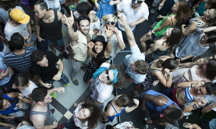 People take part in the Daybreaker dance party on a boat in in New York in the morning before going to work on Aug. 6, 2014. (Samira Bouaou/Epoch Times)