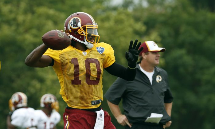 In this July 27, 2014, file photo, Washington Redskins head coach Jay Gruden, right, watches as quarterback Robert Griffin III prepares to throw during practice at the team's NFL football training facility in Richmond, Va. (AP Photo/Alex Brandon, File)