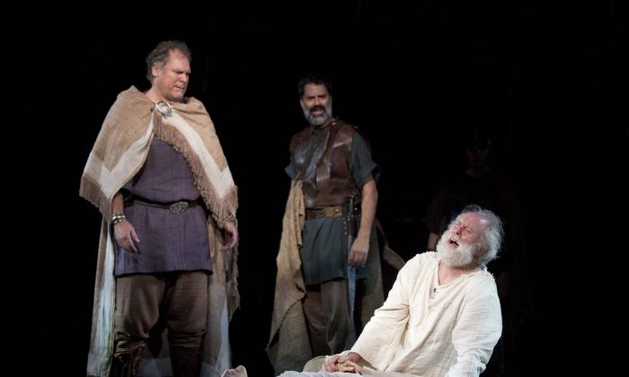 (L–R) The Earl of Kent (Jay O. Sanders) and Duke of Albany (Christopher Innvar) watch as King Lear (John Lithgow) grieves for his beloved daughter Cordelia (Jessica Collins). (Joan Marcus)