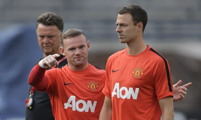 Manchester United's Wayne Rooney, left, talks with Jonny Evans as manager Louis van Gaal, left, watches during training for the their 2014 Guinness International Champions Cup soccer match against Real Madrid at Michigan Stadium in Ann Arbor, Mich., Friday, Aug. 1, 2014. (AP Photo/Paul Sancya)