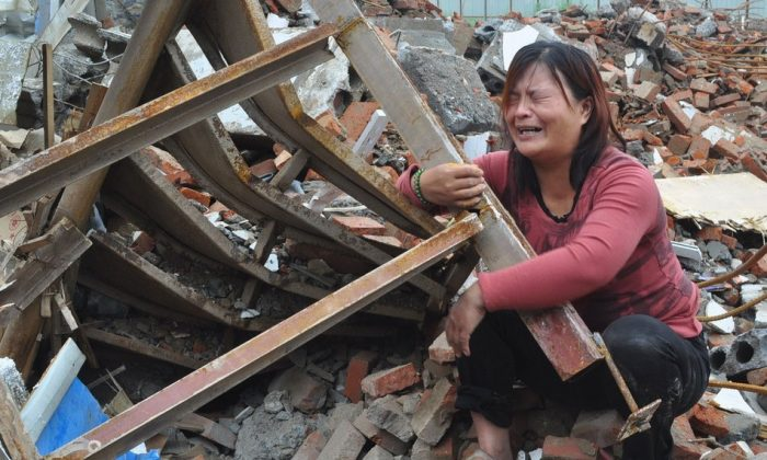 Zhang Hongwei's wife kneels among the rubble of her home and cries, in Xinzheng City of central China's Henan Province, Aug 8, 2014. Zhang and his wife were kidnapped by a group of anonymous men who burst in on them while sleeping. When the couple was released a few hours later, they found their home was demolished. (Screenshot/163.com)