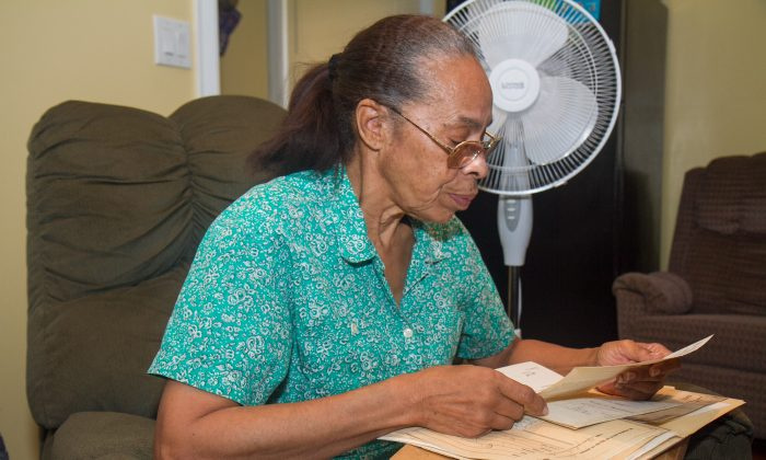 Judith Farrington goes through documents in her rent controlled apartment near Riverside Park on the Upper West Side, of Manhattan on July 29, 2014.  Farrington has lived in her apartment for 51 years. (Benjamin Chasteen/Epoch Times)