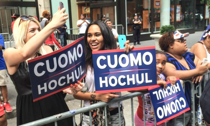 Onlookers at the Dominican Day Parade holding a Cuomo campaign poster, in Manhattan, New York, on August 10, 2014. (Jonathan Zhou/Epoch Times)