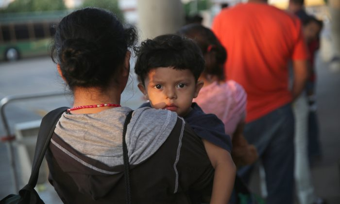 In this file photo,  Salvadorian immigrants just released from U.S. Border Patrol detention wait at the Greyhound bus station for their journey to Houston on July 25, 2014 in McAllen, Texas.  (Photo by John Moore/Getty Images)