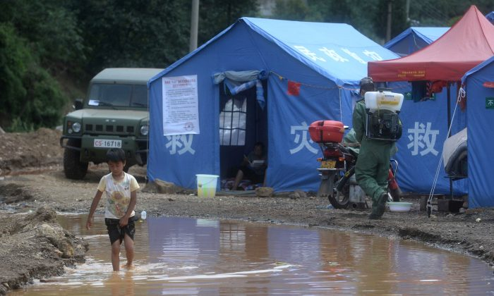A boy (L) walking through water at a temporary shelter in Longtoushan Township in southwest China's Yunnan province, on Aug. 7, 2014. Local officials are taking advantage of the disaster to gain wealth by selling donated bottled water and food to victims. (AFP/Getty Images)