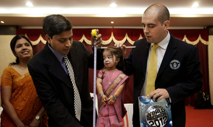 Guinness World Records adjudicator Rob Molloy, right, and Dr. Manoj Pahukar of Wockhardt hospital, second left, measure Jyoti Amge,18 years, at a press conference in Nagpur, India, Friday, Dec. 16, 2011. Amge was declared shortest woman in the world measuring 62.8 centimeters (24.7 inches) by the Guinness World Records. (AP Photo/ Manish Swarup)