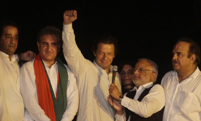Pakistan's cricketer-turned-politician Imran Khan, centre, gestures during an address to his supporters in Lahore, Pakistan, Wednesday, Aug. 13, 2014. Roads leading to the parliament in Islamabad are being blocked in run up to announced protests by Khan and anti-government cleric Tahir-ul-Qadri. Both men want the government to step down and new elections to be held. (AP Photo/K.M. Chaudary)