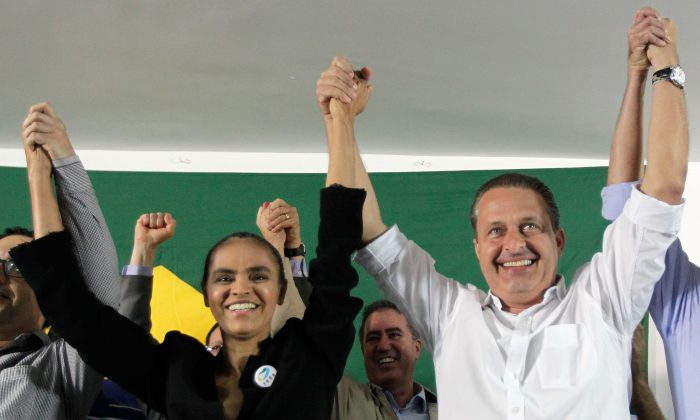 Marina Silva, left, a former senator and environment minister, and Pernambuco state Gov. Eduardo Campos, raise their arms as they celebrate her alliance with the Brazilian Socialist Party that will allow her to compete in the upcoming presidential election, in Brasilia, Brazil, Saturday, Oct. 5, 2013. The ticket is now up in the air after Campos's death on Wednesday, August 13, 2014. (AP Images)
