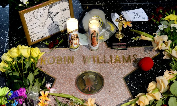 "Flowers are placed in memory of actor/comedian Robin Williams on his Walk of Fame star in the Hollywood district of Los Angeles, Monday, Aug. 11, 2014. Williams, a brilliant shapeshifter who could channel his frenetic energy into delightful comic characters like ""Mrs. Doubtfire"" or harness it into richly nuanced work like his Oscar-winning turn in ""Good Will Hunting,"" died Monday in an apparent suicide. He was 63. Williams was pronounced dead at his San Francisco Bay Area home Monday, according to the sheriff's office in Marin County, north of San Francisco. (AP Photo/Kevork Djansezian)"
