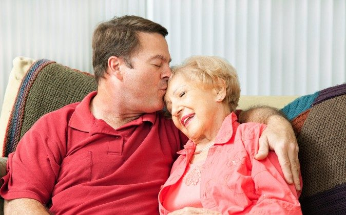 Senior woman gets a kiss from her loving adult son who has come to visit her in the nursing home. (Shutterstock*)