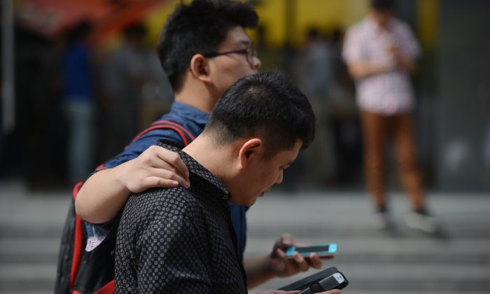 Two men use their mobile devices on a street in Shanghai on Sept. 25, 2013. Officials and civil servants working for government departments and in Communist Party offices in Shanghai have flocked to purchase cellphones with encryption, while an anti-corruption inspection is taking place in Shanghai. (Peter Parks/AFP/Getty Images)