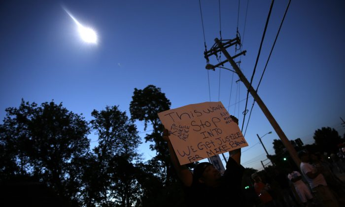 A protester holds up a sign as a police helicopter circles overhead Wednesday, Aug. 13, 2014, in Ferguson, Mo. Protests in the St. Louis suburb rocked by racial unrest since a white police officer shot an unarmed black teenager to death turned violent Wednesday night, with some people lobbing Molotov cocktails and other objects at police who responded with smoke bombs and tear gas to disperse the crowd. (AP Photo/Jeff Roberson)