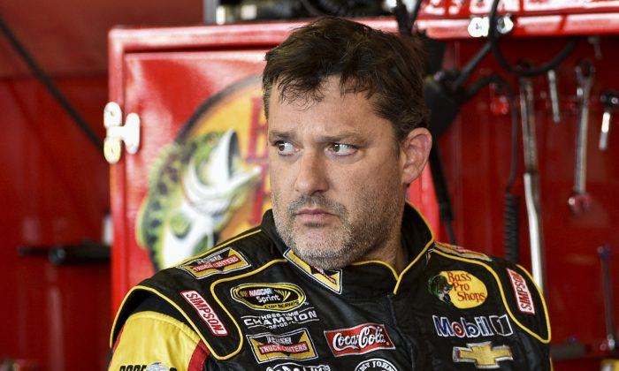 """An article saying NASCAR driver Tony Stewart will retire from racing is nothing more than a hoax. In this Friday, Aug. 8, 2014 photograph, Tony Stewart stands in the garage area after a practice session for Sunday's NASCAR Sprint Cup Series auto race at Watkins Glen International, in Watkins Glen N.Y.  Stewart struck and killed Kevin Ward Jr., 20, a sprint car driver who had climbed from his car and was on the track trying to confront Stewart during a race at Canandaigua Motorsports Park in upstate New York on Saturday night. Ontario County Sheriff Philip Povero said his department's investigation is not criminal and that Stewart was """"fully cooperative"""" and appeared """"very upset"""" over what had happened. (AP Photo/Derik Hamilton)"""