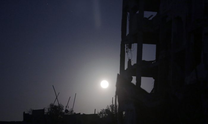 In this Aug. 11, 2014, photo a full moonshines on the destroyed al-Nada Towers residential neighborhood in the town of Beit Lahiya, northern Gaza Strip. Dozens of residents the al-Nada Towers took advantage of the latest truce to visit their homes, salvage what they can and exchange tips on how best to seek and secure compensation for their homes. (AP Photo/Khalil Hamra)