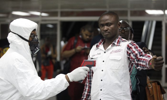 In this Aug. 6, 2014 file photo, a Nigerian port health official uses a thermometer on a worker at the arrivals hall of Murtala Muhammed International Airport in Lagos, Nigeria. As the Ebola outbreak in West Africa grows, airlines around the globe are closely monitoring the situation but have yet to make any drastic changes. (AP Photo/Sunday Alamba, File)