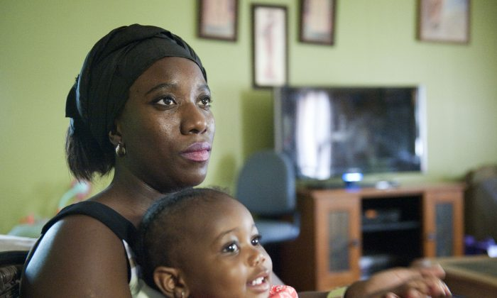 Decontee Sawyer, wife of Liberian government official Patrick Sawyer, a U.S. citizen who died from Ebola after traveling from Liberia to Nigeria, cradles her 1-year-old daughter Bella at her home in Coon Rapids, Minn., Tuesday, July 29, 2014. (AP Photo/Craig Lassig)
