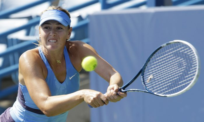 Maria Sharapova, from Russia, returns a serve against Anastasia Pavlyuchenkova, from Russia, during a match at the Western & Southern Open tennis tournament, Thursday, Aug. 14, 2014, in Mason, Ohio. (AP Photo/Al Behrman)