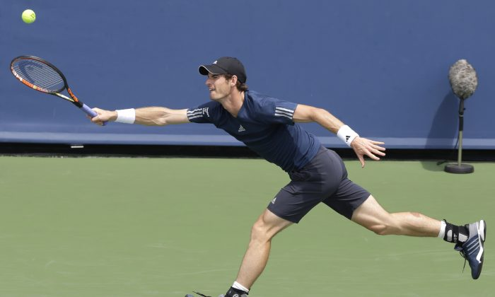 Andy Murray, from Great Britain, returns a serve against John Isner during a match at the Western & Southern Open tennis tournament, Thursday, Aug. 14, 2014, in Mason, Ohio. (AP Photo/Al Behrman)
